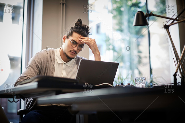 Tensed businessman looking at laptop while sitting in creative office