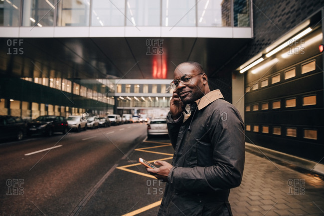 Portrait of businessman with smart phone listening music while standing on road against building in city