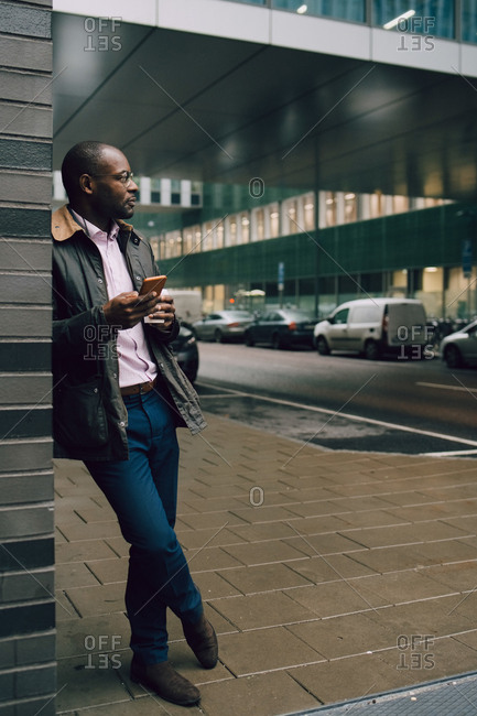 Full length of businessman with mobile phone looking away while standing on sidewalk in city