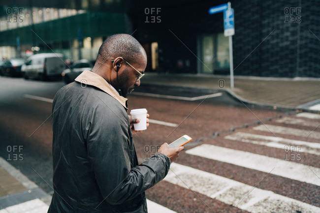 Side view of businessman with coffee using mobile phone while crossing road in city