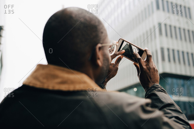 Rear view of businessman photographing modern building with smart phone in city