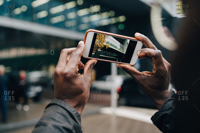 Cropped hands of businessman photographing building with smart phone in city