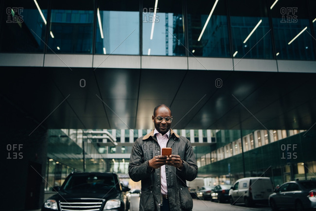 Low angle view of businessman using smart phone while standing on road against building in city