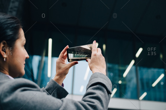 Side view of businesswoman photographing modern building with smart phone while standing in city