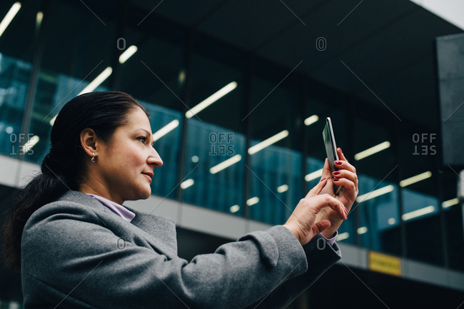 Side view of businesswoman photographing with smart phone while standing against modern building in city