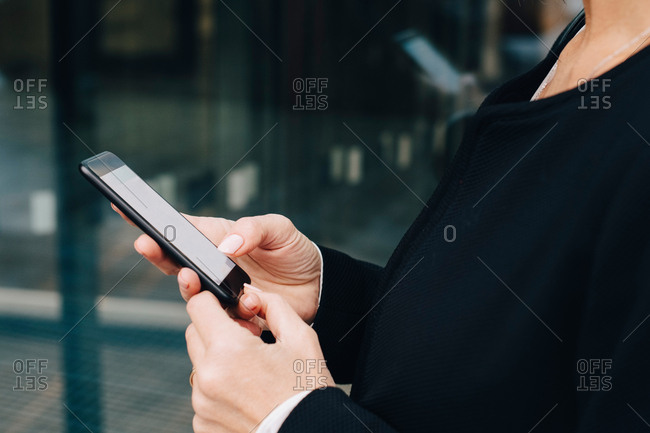 Midsection of businesswoman using smart phone while standing in city