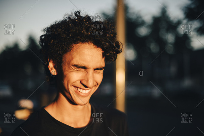 Cheerful teenage boy with eyes closed in city during sunset