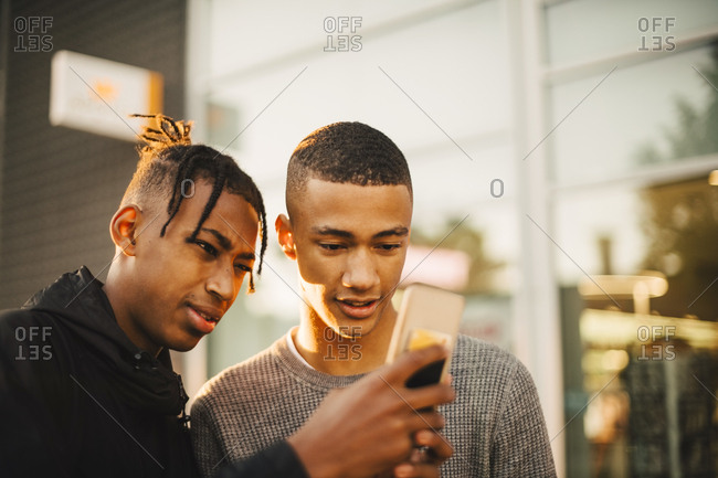 Teenage boy showing mobile phone to friend in city during sunset