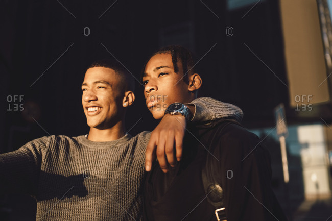 Cheerful teenage boy with arm around friend's shoulder looking away in city during sunset
