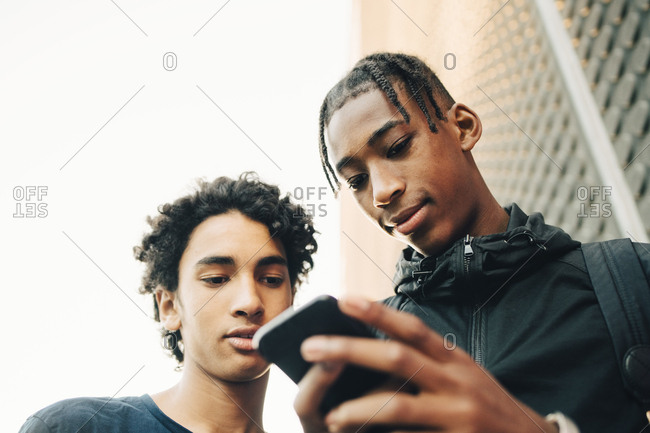 Low angle view of teenage boy showing mobile phone to friend in city