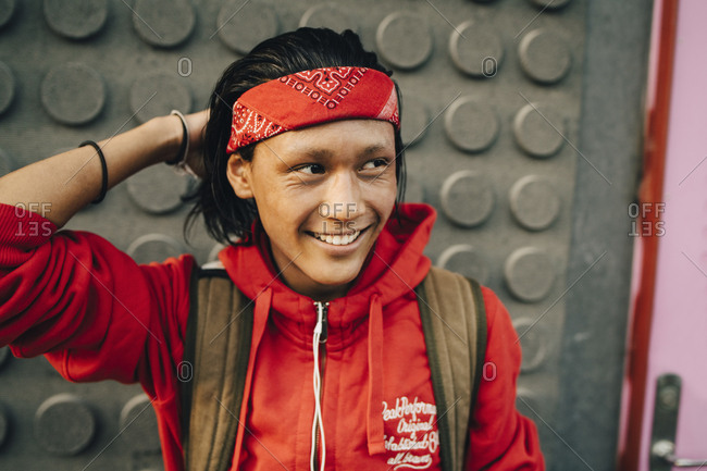 Cheerful young man wearing red bandana while looking away in city