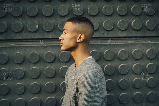 Side view of serious teenage boy looking away while standing against wall