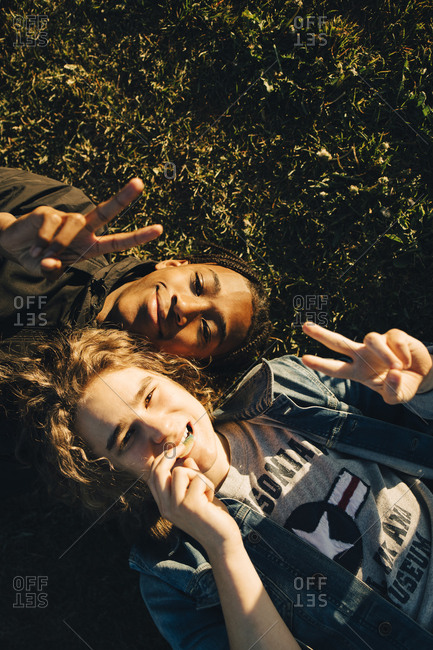 High angle portrait of smiling friends gesturing peace sign while lying on field during sunny day