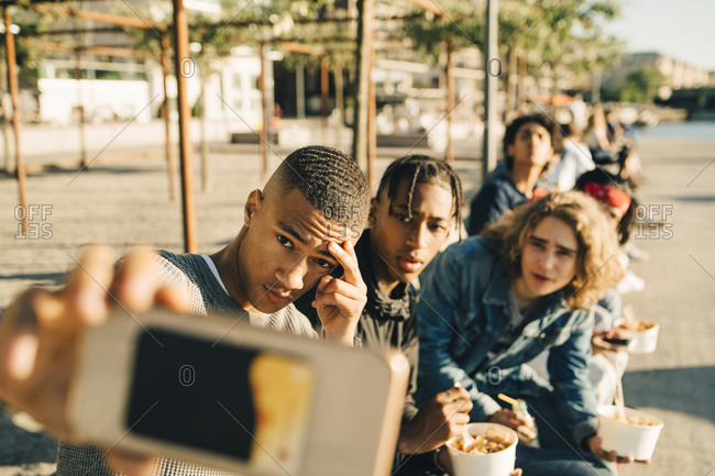 Male friends taking selfie while eating take out food on street in city