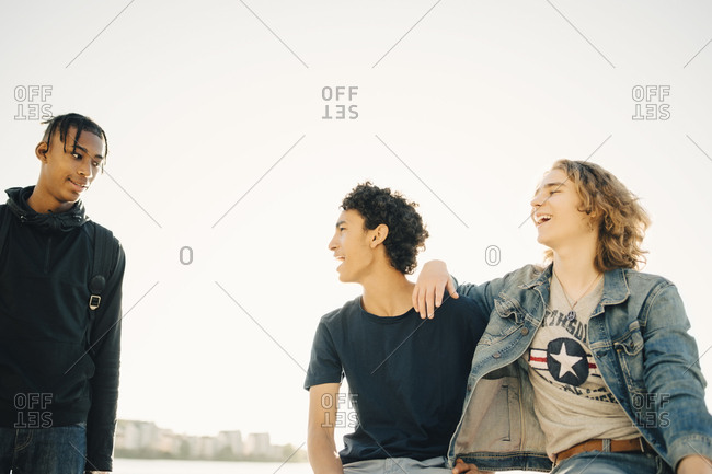 Happy male friends spending leisure time against clear sky in city