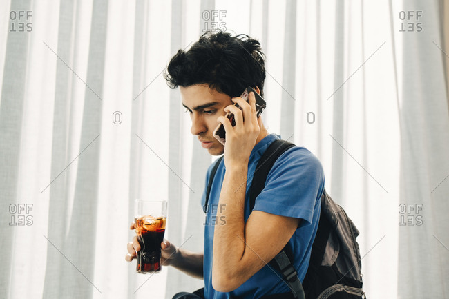 Young man answering smart phone while holding cola in restaurant