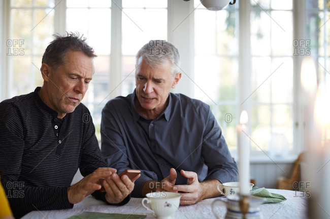 Serious mature man showing mobile phone to friend while sitting at dining table