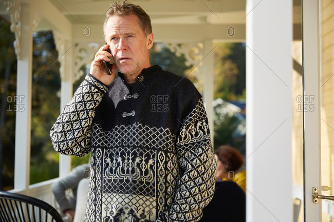 Mature man looking away while answering smart phone on porch