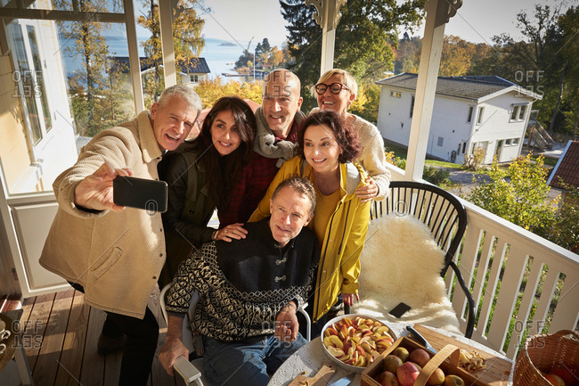 High angle view of happy mature man taking selfie with friends on porch