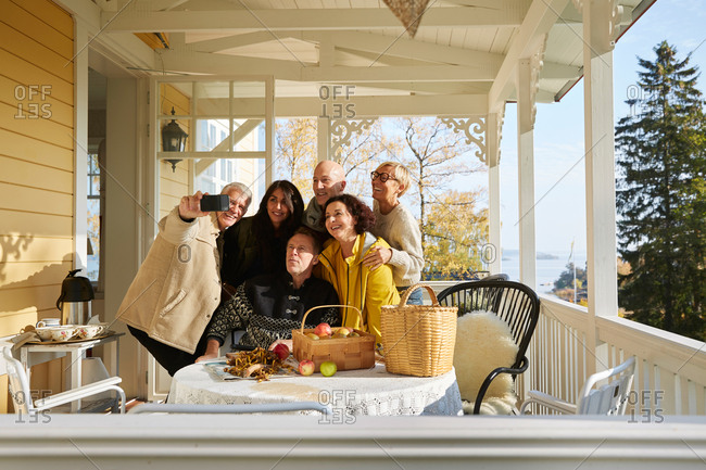 Happy mature friends posing for cell phone selfie on porch