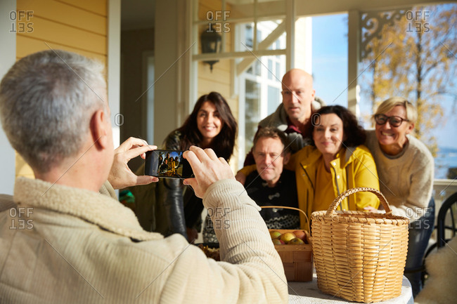 Mature man photographing friends with smart phone on porch