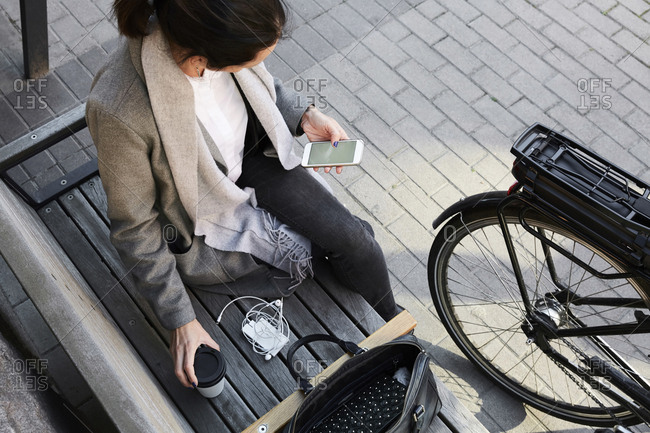High angle view of woman surfing net through mobile phone while sitting on bench in city