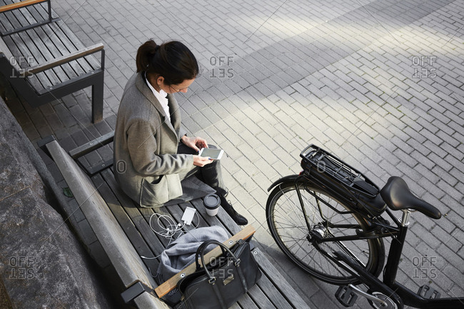 High angle view of woman surfing net through smart phone while sitting on bench in city