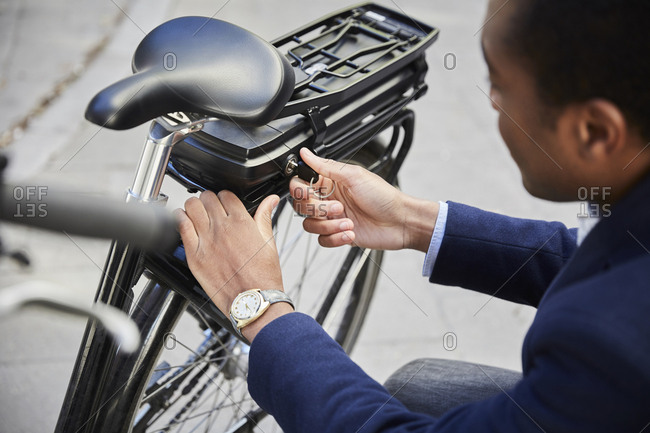High angle view of young male commuter locking electric bicycle in city