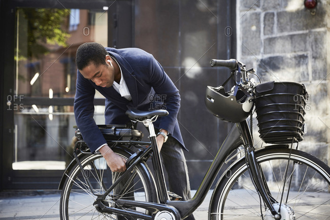 Young male commuter locking electric bicycle against building in city