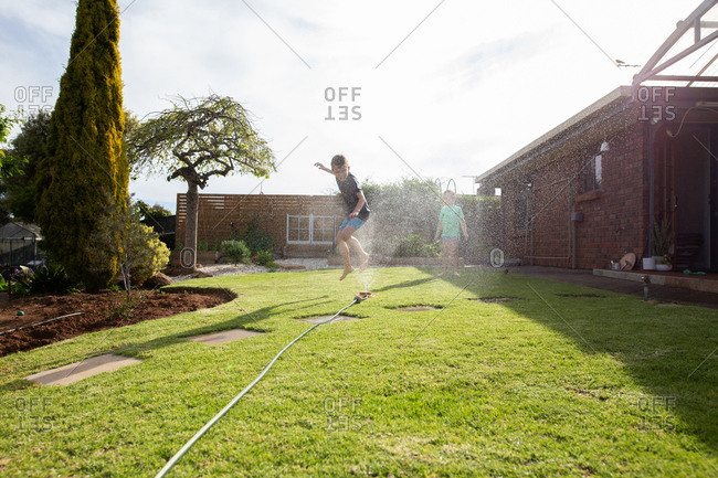 Two young kids running through a sprinkler on their front yard.