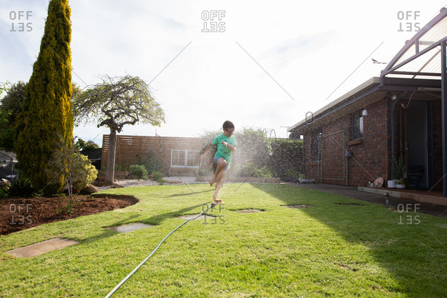 Two boys running through sprinklers in front yard.