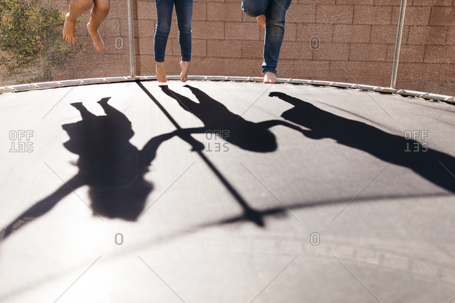 Shadows of children jumping on trampoline