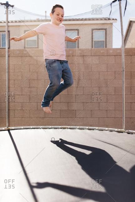 Tween boy jumping on the trampoline