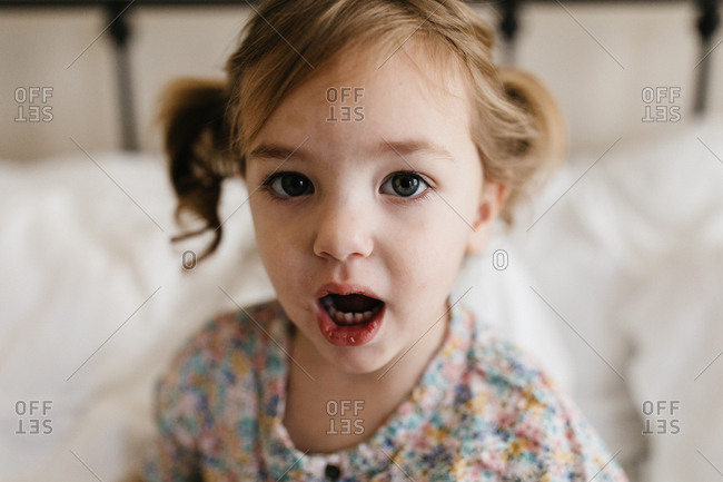 Toddler girl with pigtails on a white bed