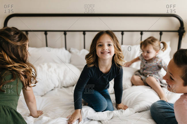 Kids jumping and playing on a bed