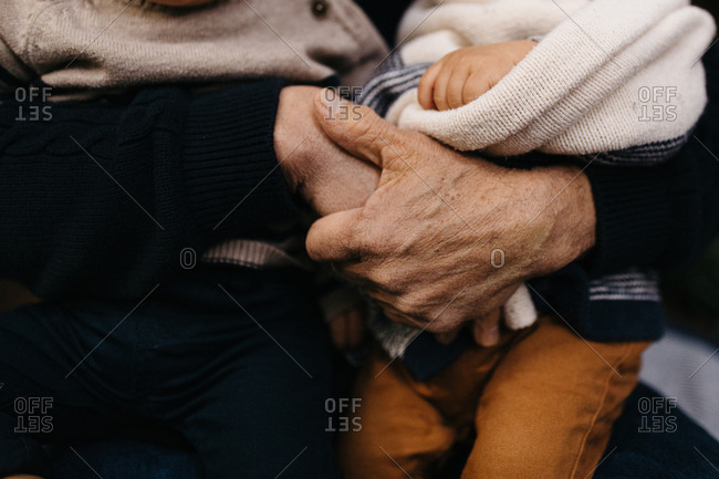 Close up of grandma's hands holding grandchildren