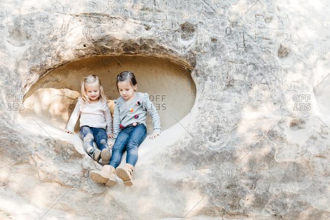 Little girls sit on rock face in Mt. Diablo, California