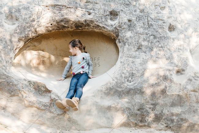 Little girl sitting on rock face in Mt. Diablo, California
