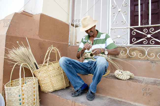 Street vendor weaving animal shapes out of palm fronds in Trinidad, Cuba