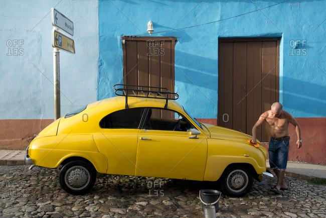 Trinidad, Cuba - May 27, 2017: Man washing his car, early morning