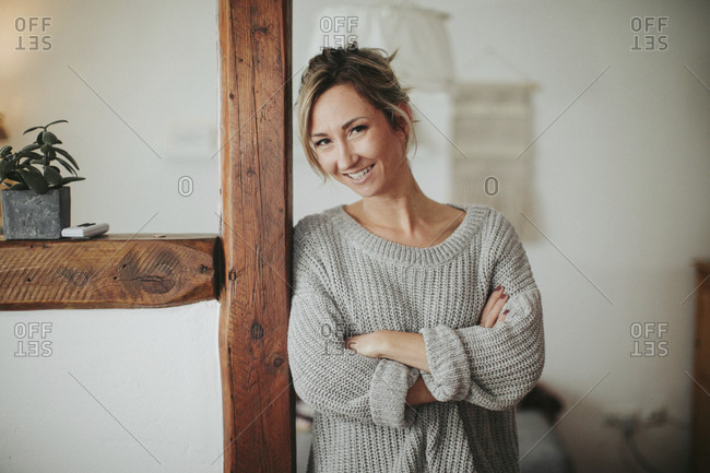 Young woman in her apartment, arms crossed, smiling, half portrait