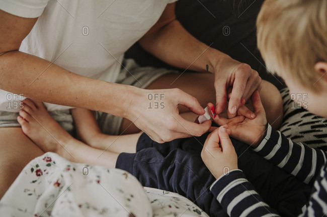 In bed in the morning, mother is wounding her son's finger.