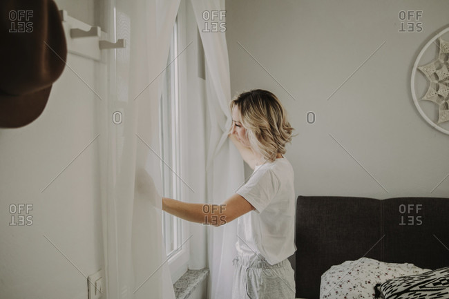 Woman stands at the bedroom window and opens the curtains