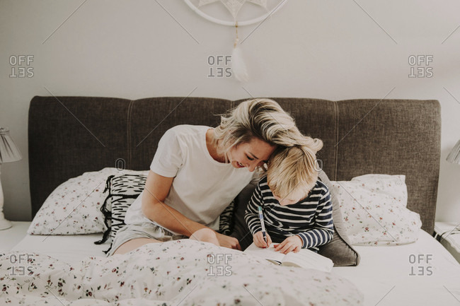 Mother and son in bed, boy writes in a book