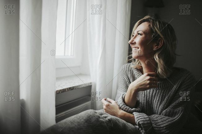 Woman looks joyfully out the window