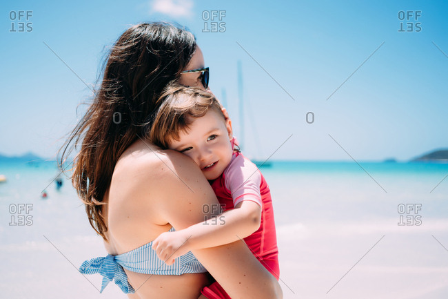 Mother and happy toddler daughter embrace on Whitsunday Islands beach, Great Barrier Reef, Queensland, Australia.