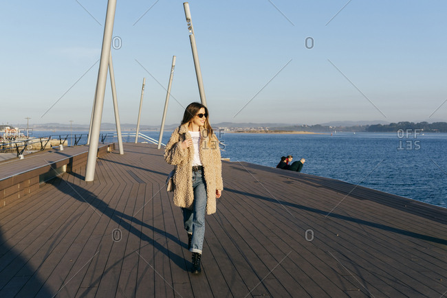Trendy blonde girl walking on the pier on a sunny afternoon