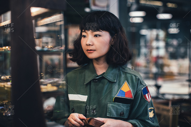 Pretty Asian woman working at vintage army shop.