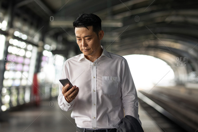 Middle-aged Asian businessman standing at metro station and using his cell phone.