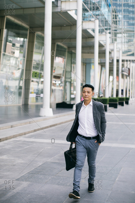 Middle-aged Asian businessman walking outdoors.